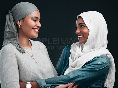 Buy stock photo Cropped shot of two attractive young women wearing hijabs and embracing each other against a black background in the studio