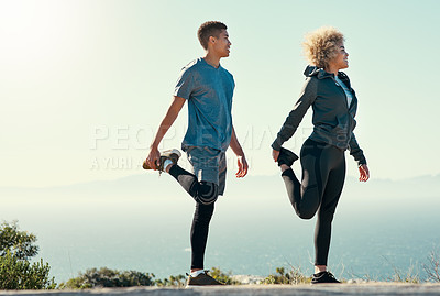 Buy stock photo Shot of a young couple warming up before their run