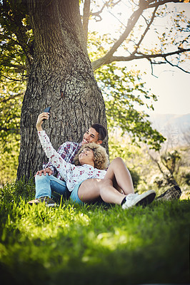 Buy stock photo Shot of a young couple taking a selfie while spending the day at the park