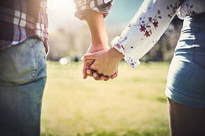 Buy stock photo Cropped shot of an unrecognizable couple holding hands outdoors