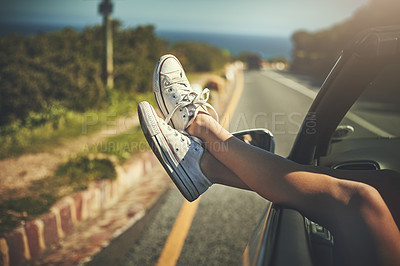 Buy stock photo Cropped shot of an unrecognizable woman putting her feet up while on a road trip