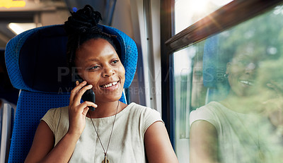 Buy stock photo Cropped shot of an attractive young woman sitting alone in a train and talking on her cellphone