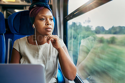 Buy stock photo Cropped shot of an attractive young woman sitting alone in a train and looking contemplative while wearing earphones