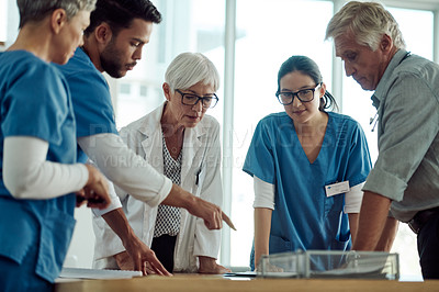 Buy stock photo Cropped shot of two confident mature doctor's having a discussion with three nurses while pointing at a digital tablet inside of an office during the day