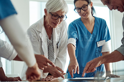 Buy stock photo Cropped shot of two confident mature doctor's having a discussion with two nurses while pointing at a digital tablet inside of an office during the day