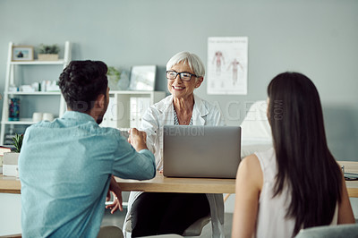 Buy stock photo Cropped shot of a confident mature female doctor meeting with a young couple in her office at the hospital