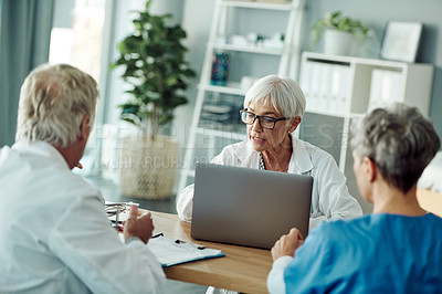 Buy stock photo Cropped shot of a confident mature doctor having a discussion with another doctor and a nurse while being seated at a desk inside an office