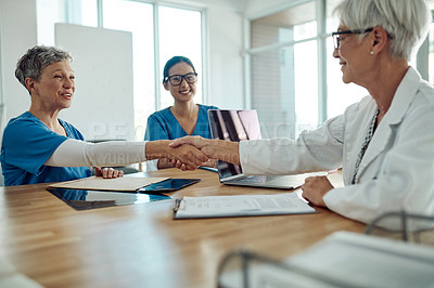 Buy stock photo Something like this would sound better: Cropped shot of two confident mature doctors shaking hands while having a discussion together their office