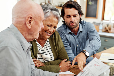 Buy stock photo Cropped shot of a handsome young businessman sitting with his senior clients and explaining paperwork to them during a meeting