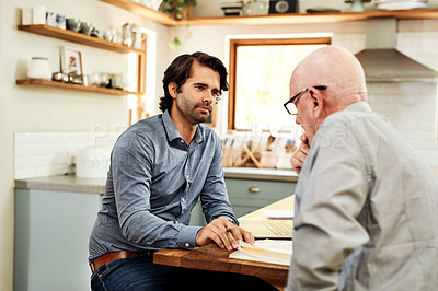 Buy stock photo Cropped shot of a handsome young businessman sitting with his senior client in their home and discussing their finances