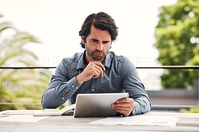 Buy stock photo Cropped shot of a handsome young businessman sitting outside alone and using a tablet to calculate his savings