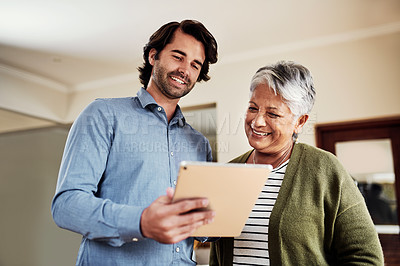 Buy stock photo Cropped shot of a handsome young businessman standing with his senior client and using a tablet to discuss her finances