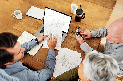 Buy stock photo High angle shot of a handsome young businessman sitting with his senior clients and explaining their financial paperwork