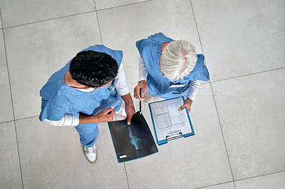 Buy stock photo High angle shot of two medical practitioners analysing x-ray scans in a hospital