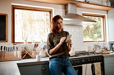 Buy stock photo Cropped shot of an attractive young woman using a smartphone while standing in her kitchen at home