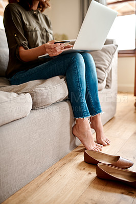Buy stock photo Cropped shot of an unrecognizable woman using a laptop and a credit card to shop online while sitting in her living room at home