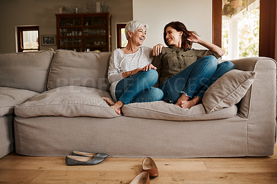 Buy stock photo Full length shot of an affectionate young woman having a chat with her elderly mother in their living room at home
