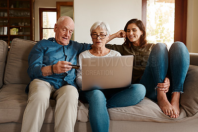 Buy stock photo Cropped shot of an affectionate senior couple using a laptop to shop online while relaxing with their adult daughter at home