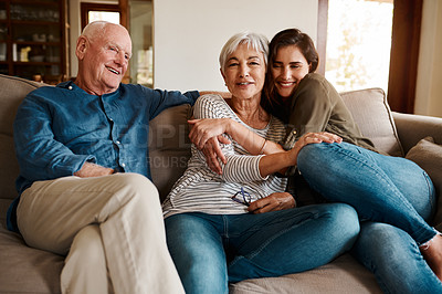 Buy stock photo Cropped shot of an affectionate young woman spending time with her elderly parents in their living room at home