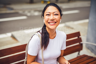 Buy stock photo Cropped portrait of an attractive young woman wearing earphones and sitting alone on a street bench during a vacation
