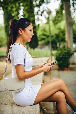 Buy stock photo Cropped shot of an attractive young woman sitting alone in the park and using her cellphone during a vacation