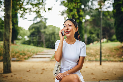 Buy stock photo Cropped shot of an attractive young woman sitting alone in the park and talking on her cellphone during a vacation