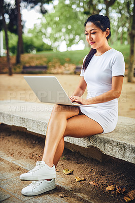 Buy stock photo Full length shot of an attractive young woman sitting alone in the park and using her laptop during a vacation