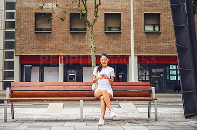 Buy stock photo Full length shot of an attractive young woman wearing earphones and using her cellphone while sitting on a street bench