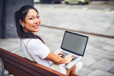 Buy stock photo Cropped portrait of an attractive young woman wearing earphone and sitting on a street bench while using her laptop