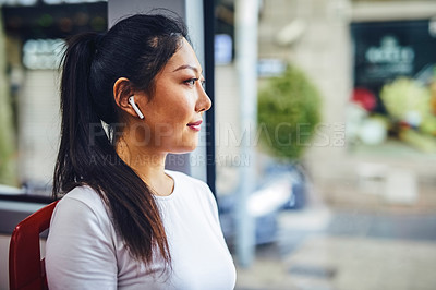 Buy stock photo Cropped shot of an attractive young woman wearing earphones and sitting alone in a bus during a vacation
