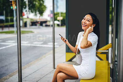 Buy stock photo Cropped portrait of an attractive young woman wearing earphones and using her cellphone while sitting in a bus stop