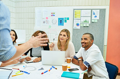 Buy stock photo Shot of a group of young designers listening attentively during a meeting with other colleagues at work
