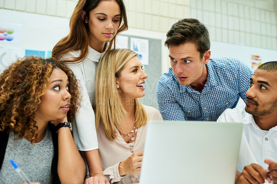 Buy stock photo Cropped shot of a group of young designers working on a laptop together during their meeting at work