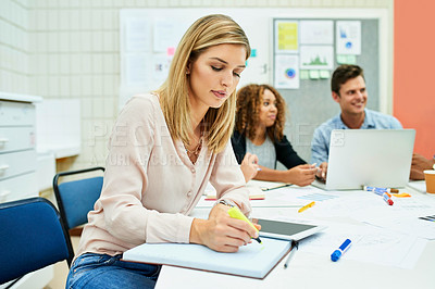 Buy stock photo Shot of an attractive young designer taking down some notes during a meeting with colleagues at work
