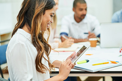 Buy stock photo Shot of an attractive young designer using a digital tablet during a meeting with colleagues at work