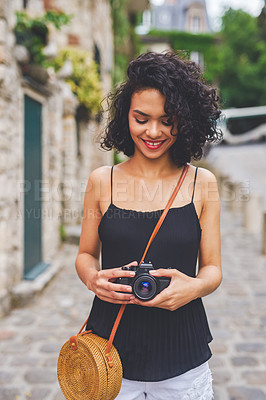 Buy stock photo Shot of an attractive young woman holding her camera while out exploring a city