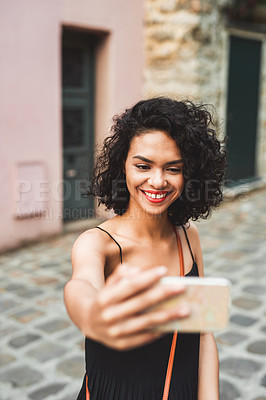 Buy stock photo Shot of an attractive young woman taking a selfie while exploring a city