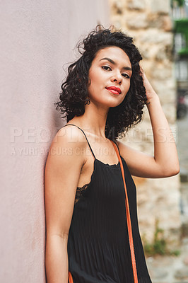 Buy stock photo Shot of an attractive young woman leaning against a wall outside