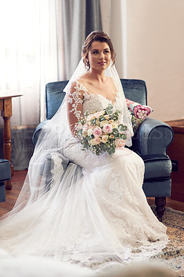 Buy stock photo Shot of a beautiful young bride sitting on a couch on her wedding day