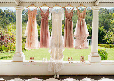Buy stock photo Shot of a wedding dress and bridesmaid dresses hanging together outdoors