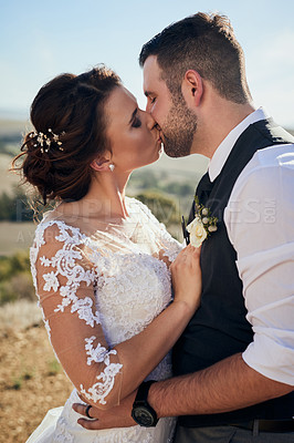 Buy stock photo Shot of a young couple kissing outside on their wedding day