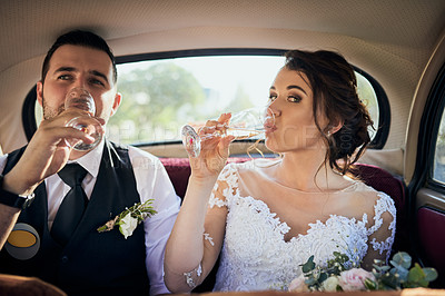 Buy stock photo Shot of a young couple drinking wine while travelling in a car on their wedding day