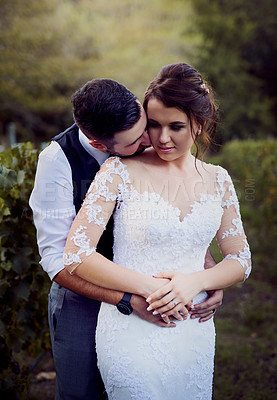 Buy stock photo Shot of a young couple standing outside on their wedding day