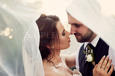 Buy stock photo Shot of a young couple standing under a veil on their wedding day