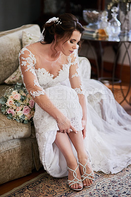 Buy stock photo Shot of a beautiful young bride adjusting her sandals on her wedding day
