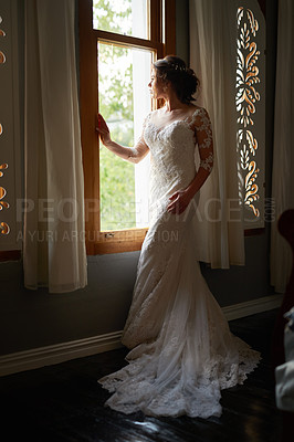 Buy stock photo Shot of a beautiful young bride looking through a window on her wedding day