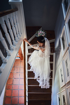 Buy stock photo High angle shot of a beautiful young bride walking up a staircase on her wedding day