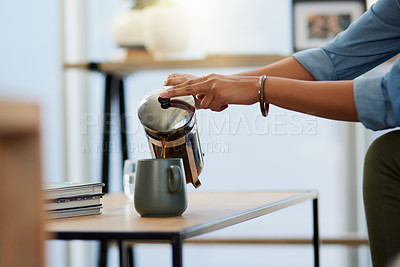 Buy stock photo Cropped shot of an unrecognizable young woman pouring herself a cup of coffee while relaxing at home