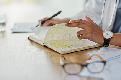 Buy stock photo Closeup shot of an unrecognisable doctor writing in a notebook in her office