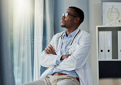 Buy stock photo Shot of a young doctor looking thoughtful while sitting in his office